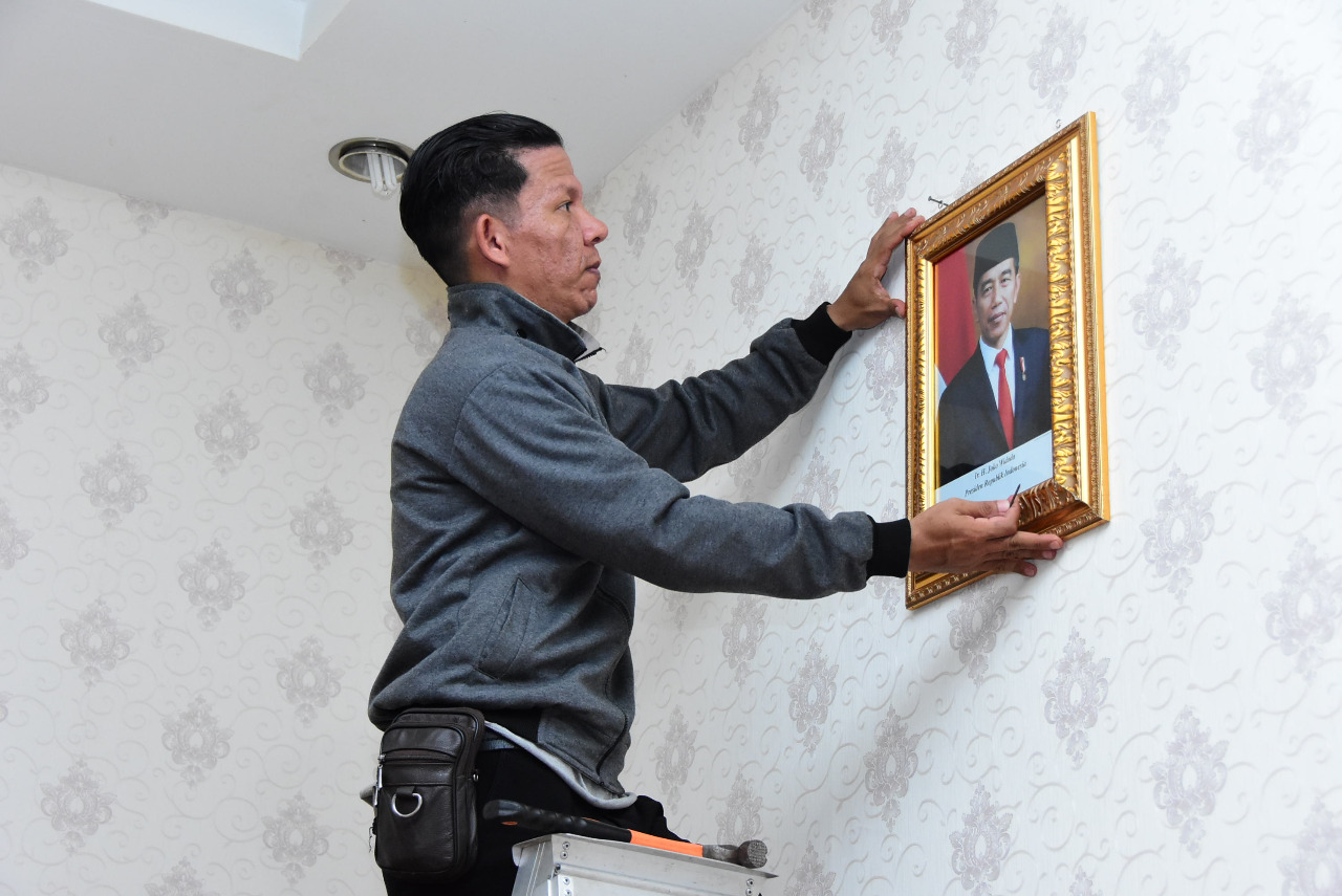 Omi Widono petugas Satpam Diskominfotik memasang foto Presiden Ir Joko Widodo