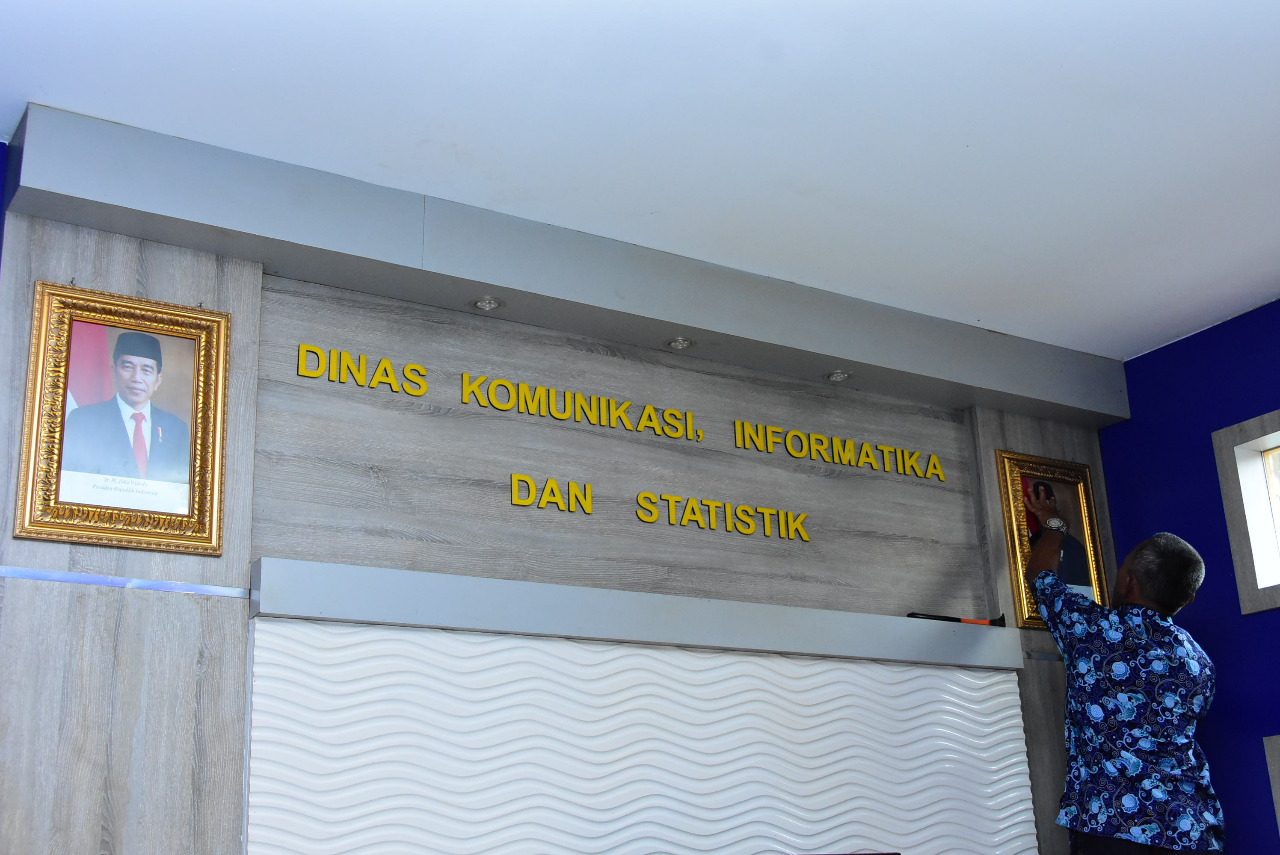 Syahrudin petugas Satpam Diskominfotik memasang foto Presiden Ir Joko Widodo dan Wakil Presiden KH Ma'ruf Amin