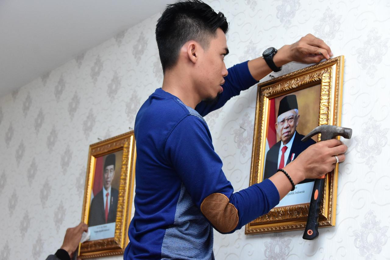 Eka staf Sekretariat Diskominfotik memasang foto Wakil Presiden KH Ma'aruf Amin