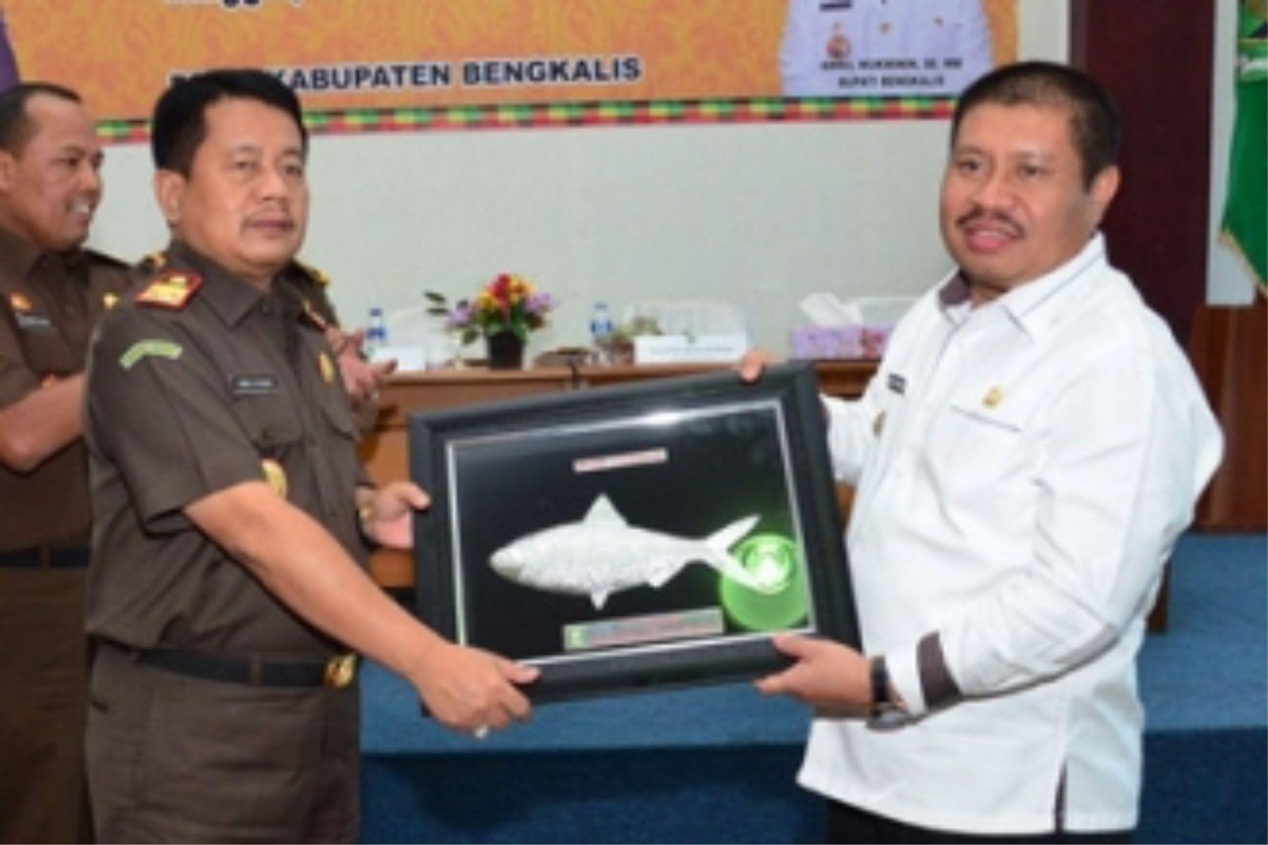 Bupati Amril Mukminin menyerahkan cendramata kepada Uung Abdul Syakur saat menjabat Kajati Riau dalam sebuah kesempatan di Pekanbaru